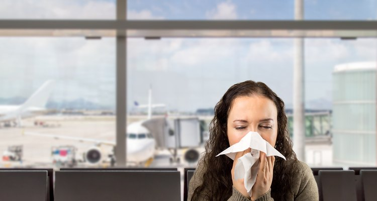 Woman blowing her nose with a tissue at the  airport