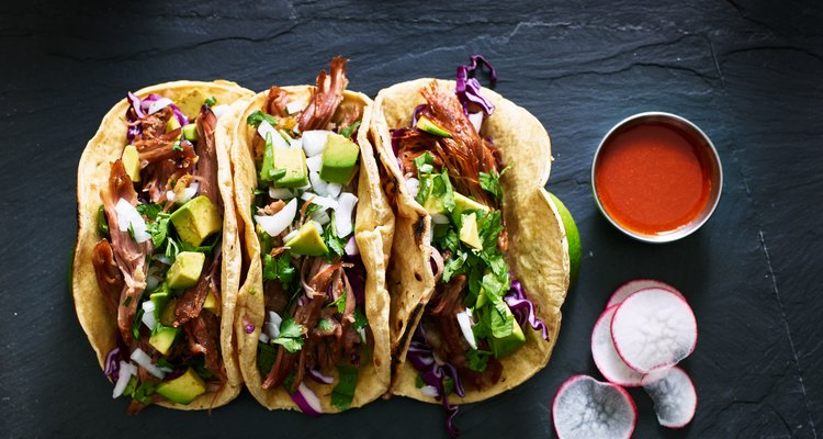 three mexican pork carnitas tacos flat lay composition
