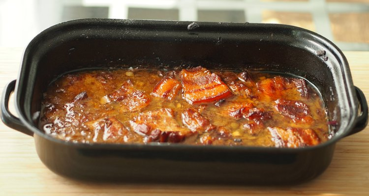 Baked pork belly with a sauce in a black roasting pan on a wooden table. Traditional specialty form the Czech Republic called 'moravsky vrabec'.