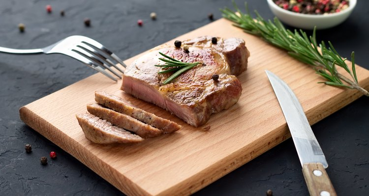 Tasty homemade well-done steak on wooden cutting board with fork and knife on stone background.