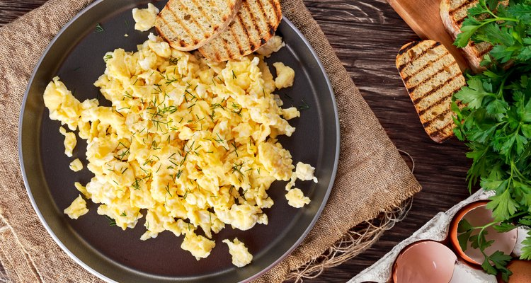 Scrambled eggs on Pan with grilled toast.
