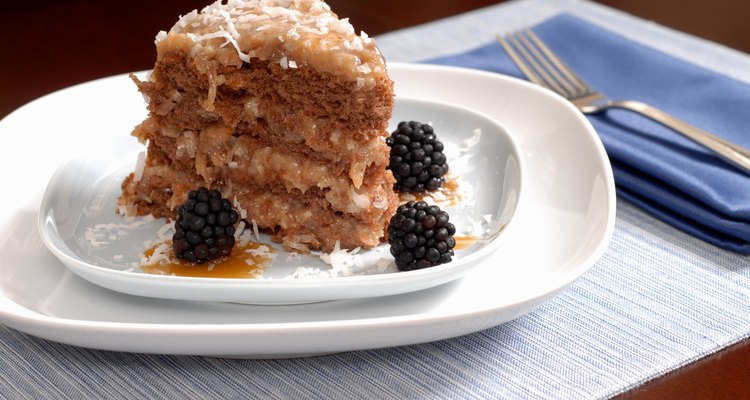 Slice of German chocolate cake on a plate with blackberries