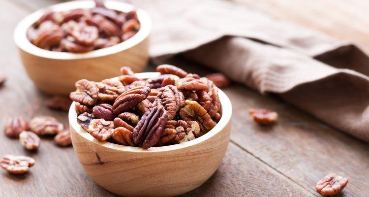 Pecan nuts in wooden bowel on wooden