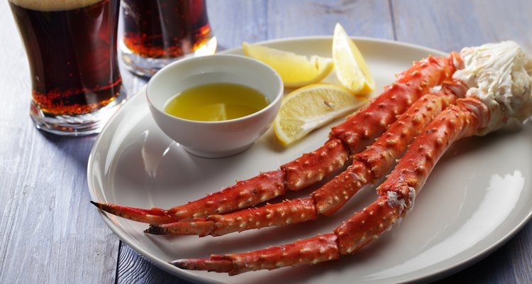 Crab legs on a serving platter with butter and lemon wedges