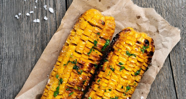 Grilled corn cobs on wooden background