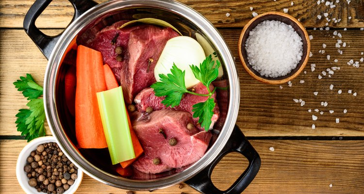Ingredients for meat broth in pan on wooden table: beef, onion, carrot, celery, parsley and spices.