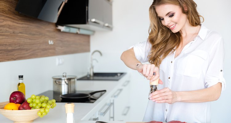 Happy beautiful young woman cooking meat on the kitchen