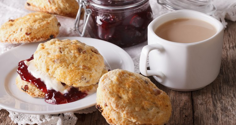 Scones with jam and tea with milk on the table