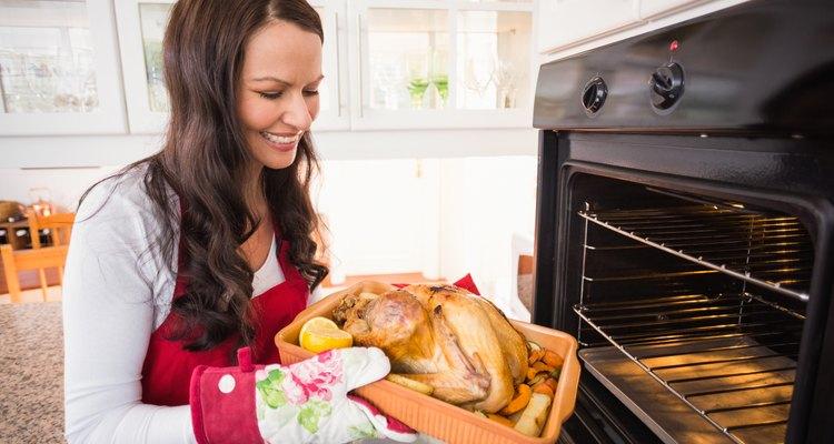 Smiling woman roasting a turkey