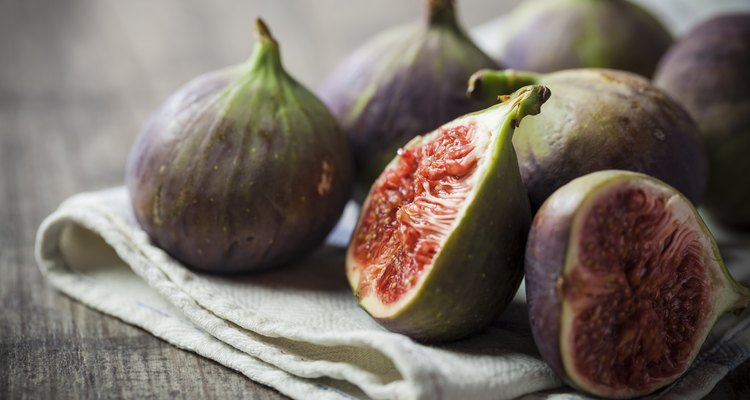 Whole and sliced figs on a folded linen on wood table
