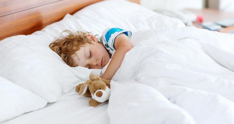 Little boy asleep in a hotel bed