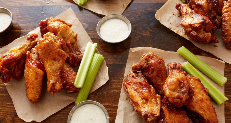 different flavored chicken wings on wooden table