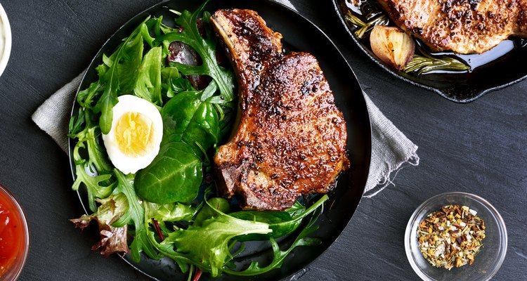 Marinaded grilled pork chop on a plate on a bed of greens