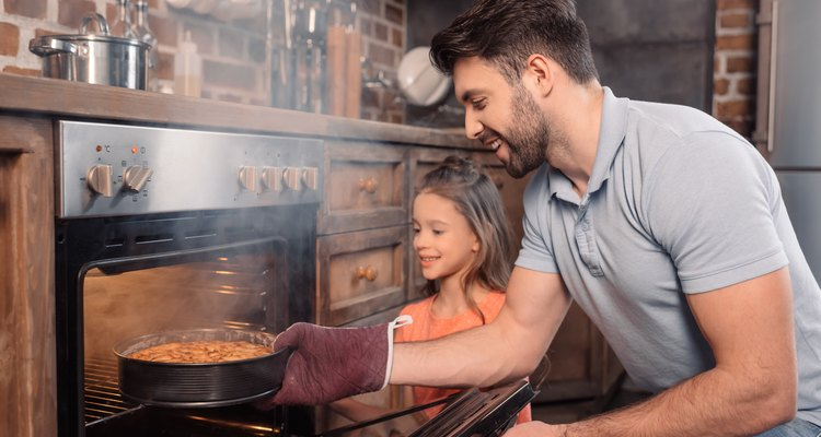smiling father and daughter taking cake from oven