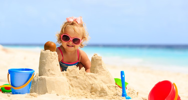 Little girl building sand castles on beach