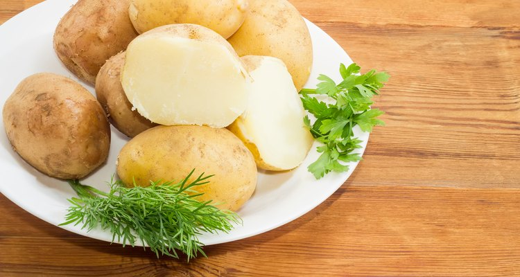 Potatoes boiled in their skins and herbs on dish closeup