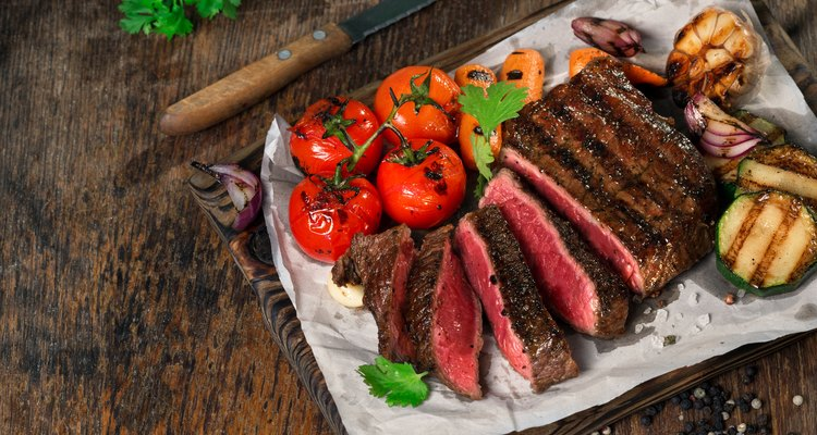 Sliced rare grilled steak on rustic cutting board with set of grilled vegetables on dark rustic wooden table with copy space