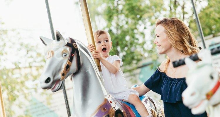 Little girl riding on a carousel