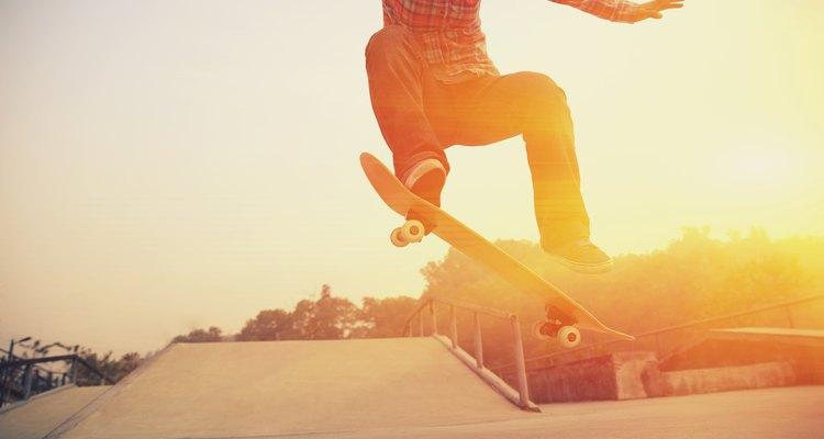 A skateboarder jumping his board at a skate park at sunset