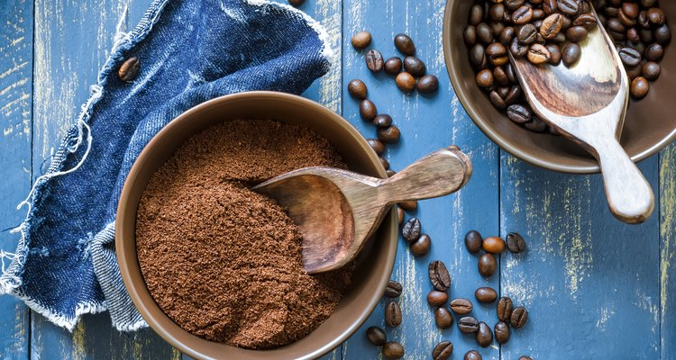 Bowls of uncut and ground coffee beans on blue wooden table