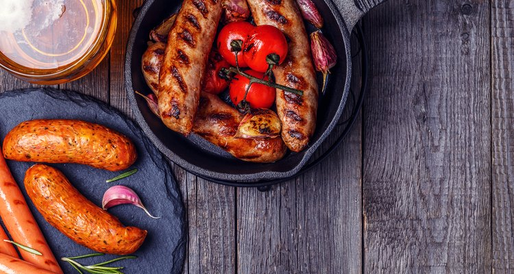 Grilled sausages with glass of beer on wooden table.
