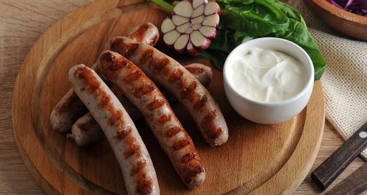 grilled bratwurst sausages with sauce, spinach and garlic