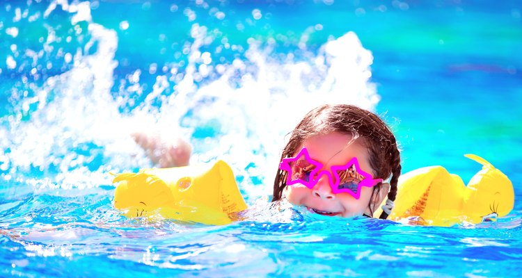 Little girl wearing water wings at a water park