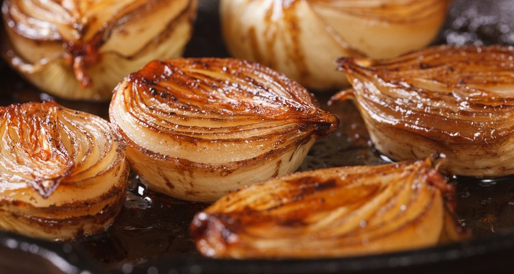 ñaramelized onion halves with balsamic vinegar in a pan