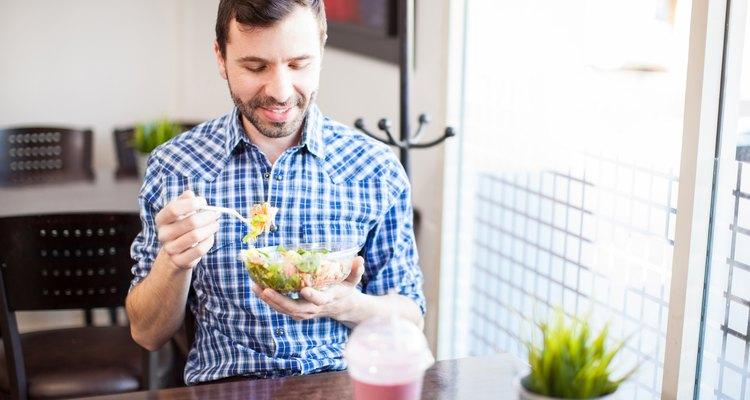 Man eating healthy tuna salad at his desk at work