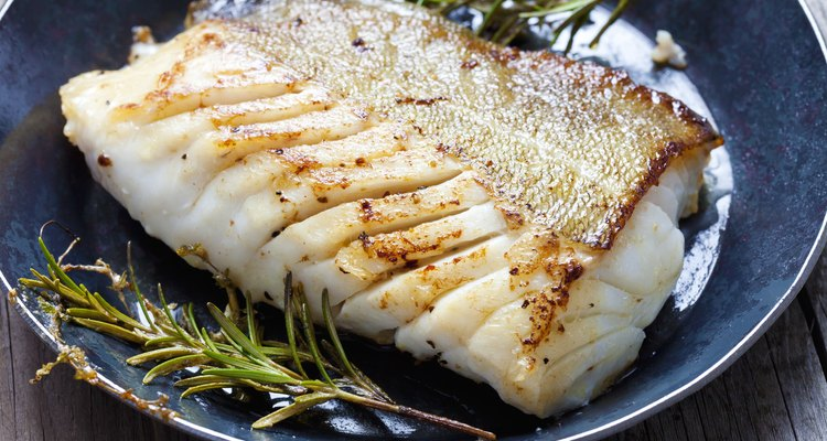 Close-up of a cod fillet with rosemary on a plate