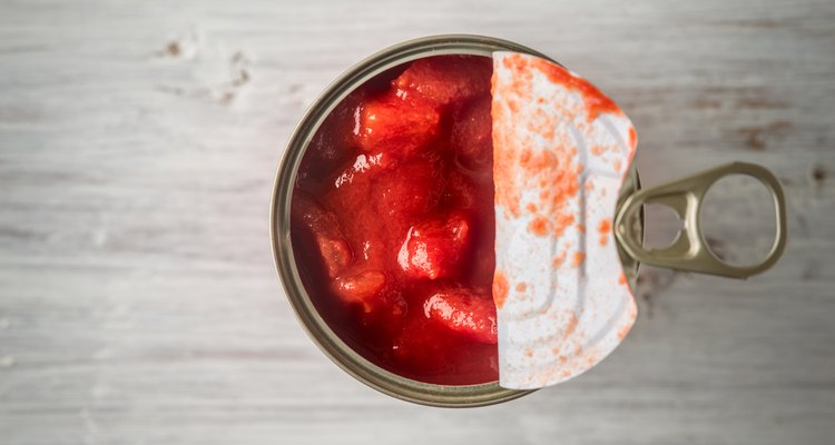 Chopped tomatoes in metal can in wooden table top view