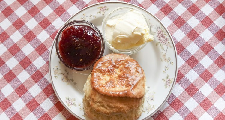 Scone and strawberry jam and clotted cream on a plate on a table with a red and white checkered table cloth