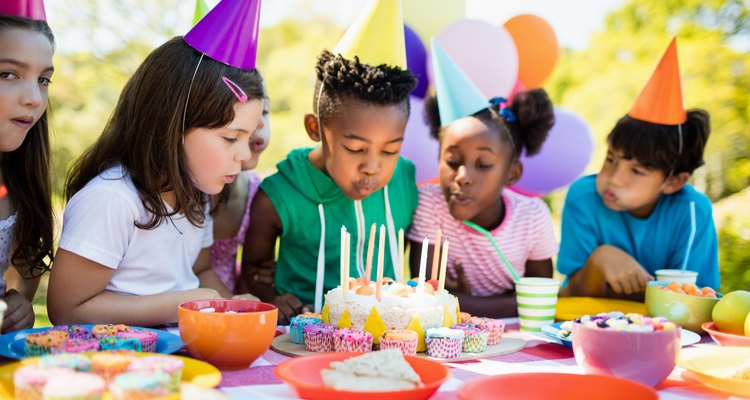 Cute children blowing together on the candle during a birthday party