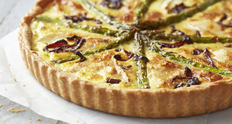 Asparagus quiche on white wooden surface