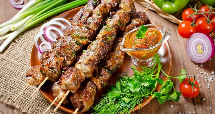 Grilled beef liver kebabs on a dark wooden background