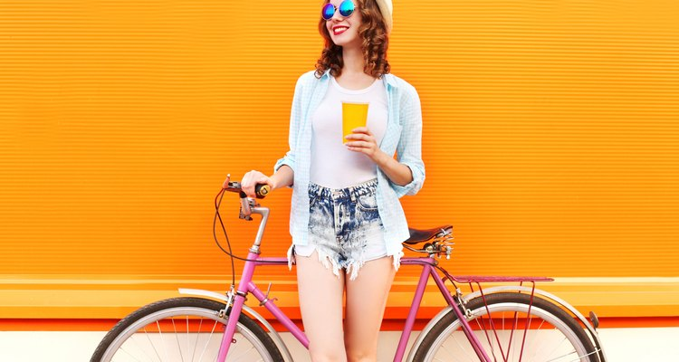 Fashion woman with coffee or juice cup and retro bicycle