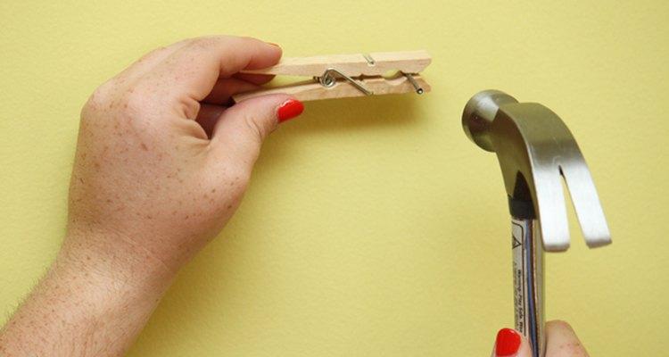 Una mujer sostiene un clavo con un broche para colgar la ropa