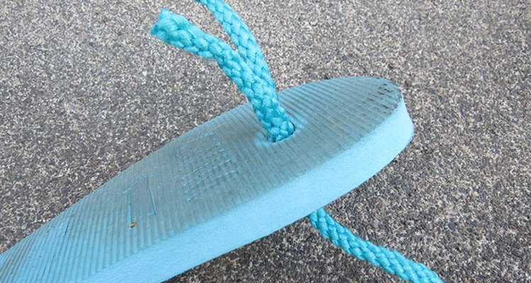 String rope through the top hole of the sole.