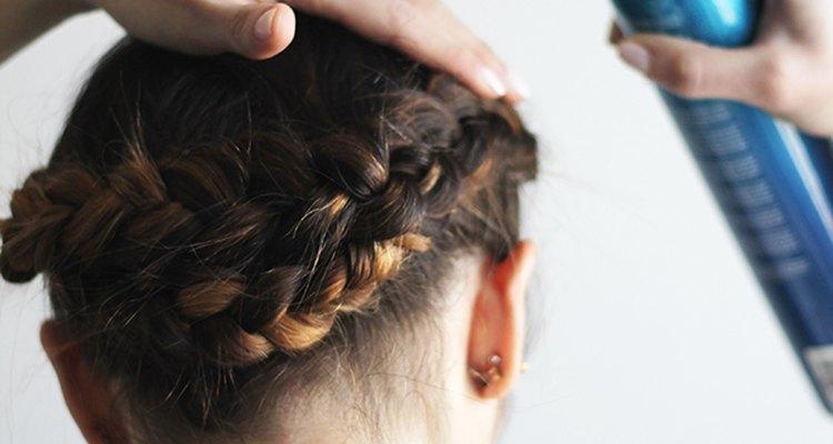 Spraying hairspray on braids