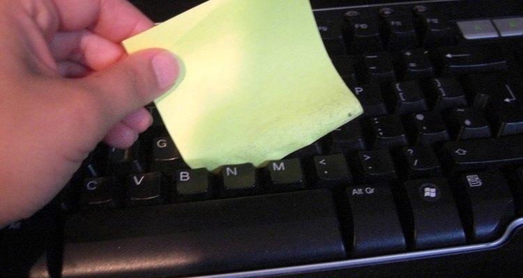 Una persona utiliza un papel con adhesivo para limpiar el teclado de la computadora