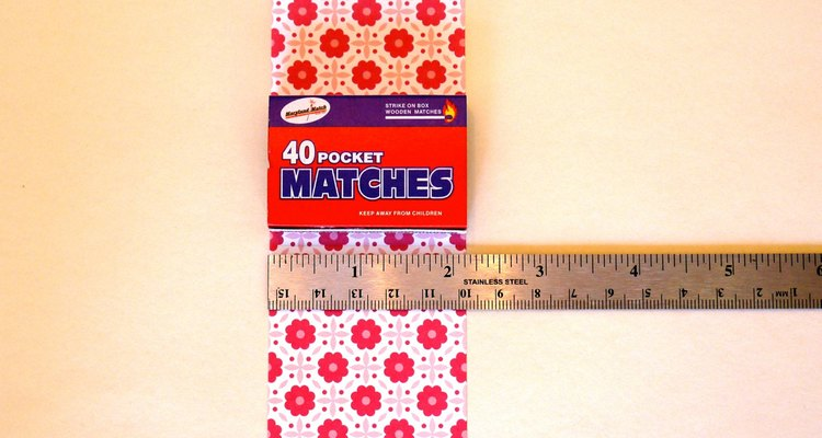 Mide y corta la tira de papel del mismo largo que la tapa.