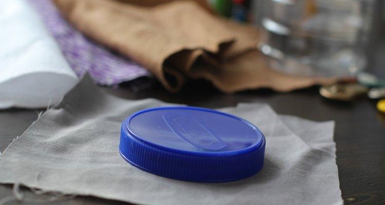 Com um resto de tecido, cubra a tampa da jarra