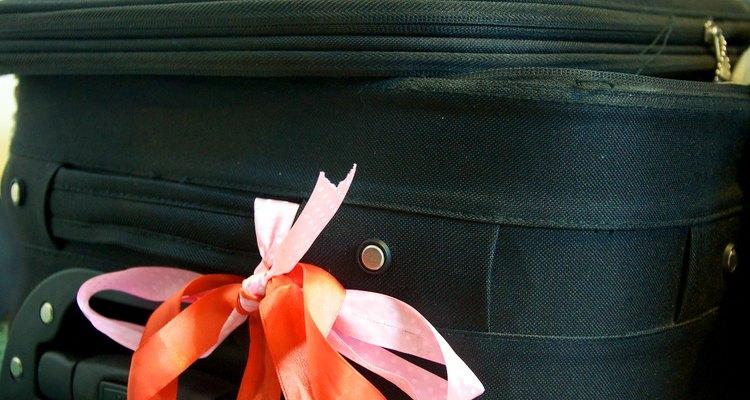 Imagen de una valija con telas de colores en sus manijas