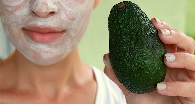 Woman in DIY face mask holding avocado