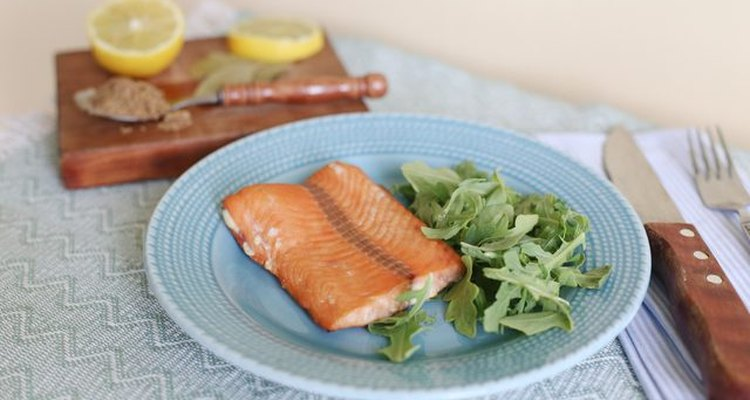 Smoked salmon next to salad greens on a blue plate