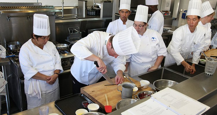 Estudiantes prestando atención mientras un profesor les enseña una técnica de corte en la cocina