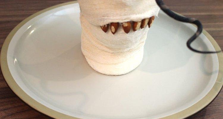 Usa gotas de pegamento para adherir la momia a la bandeja.