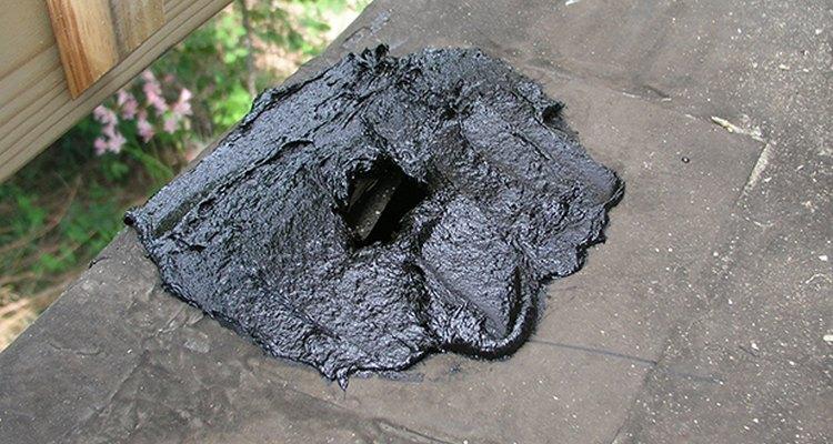 El cemento asfáltico para techos listo para poner el parche.