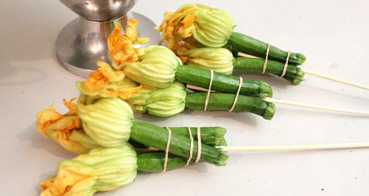 Ata las flores de calabacín con un pincho.