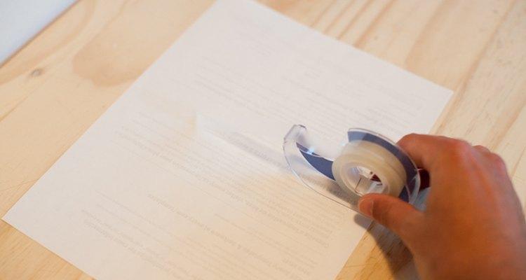 Coloca cinta adhesiva sobre las uniones perforadas de la parte posterior de las etiquetas.